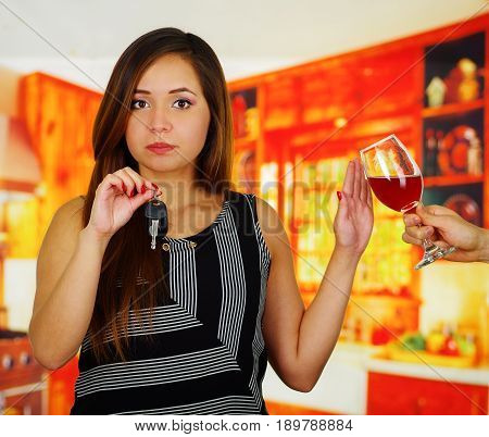 Close up of a beautiful woman holding a car keys and refusing a glass of red wine, in bar background.