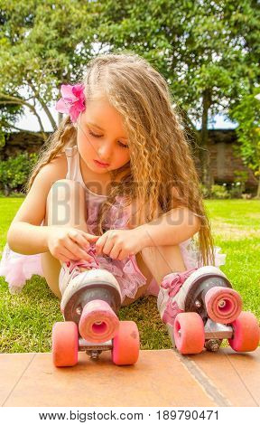 Little girl preschool beginner tie the laces of her roller skates, in a grass background.