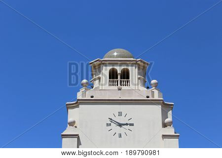 Looking up at white stucco bell tower with a light gray dome and a clock reading two fifty in Roman numerals against a bright blue clear sky