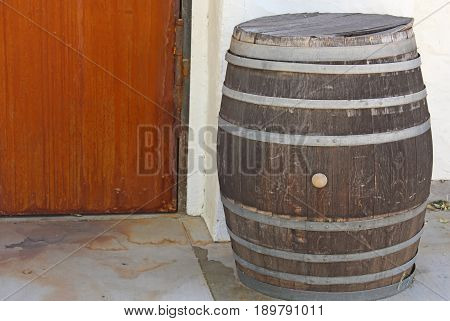 Brown wine barrel with metal trim on stained gray floor with the bottom portion of a white stucco wall with a dark red wooden door visible in the background