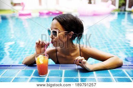 Asian woman drinking juice by the poolside
