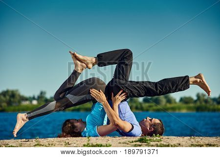 Young woman doing yoga with partner on the background of blue sky
