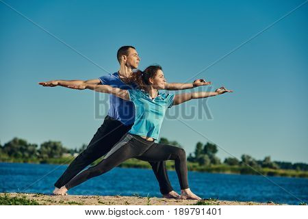 Group of two fit people working out and doing yoga