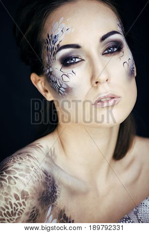 fashion portrait of pretty young woman with creative make up like a snake print, fashion victim with python skin clutch luxury