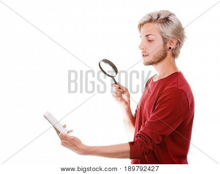 Funny young guy reading message on smart phone looking with ssurprised face expression using loupe magnifying glass isolated on white