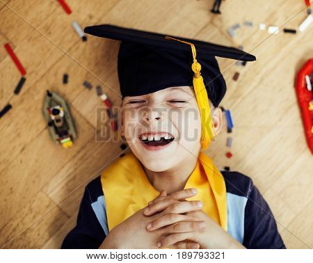 little cute preschooler boy among toys lego at home in graduate hat smiling posing emotional, lifestyle people concept, wooden floor close up