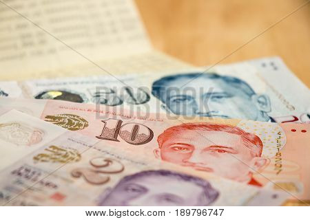 Bank passbook with Singapore dollar on wood table background