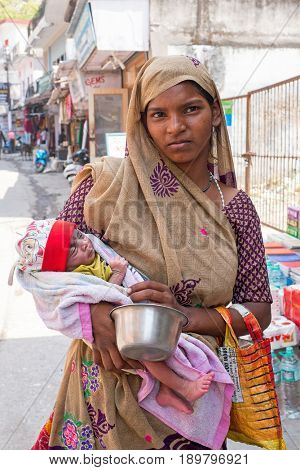 LAXMAN JHULA, INDIA - APRIL 15, 2017: Indian woman with newborn baby in the streets of Laxman Jhula in India