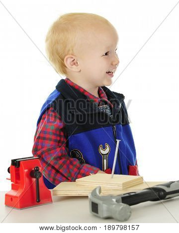 Profile of a laughing toddler playing handyman. He stands behind a table of toy tools and real wooden blocks with a nail in them.  On a white background.