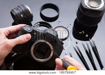Photo camera repair set in laboratory. Maintenance support of professional photo camera and lenses by engineer. Optical dslr lens and video equipment service