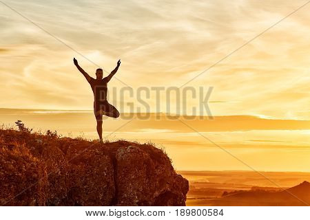 Silhouette of the man practicing yoga on the hill against beautiful sunset. Doing yoga exercises on the nature. Horizontal photo of young sportsman. Beautiful landscape and sky with clouds. Concept of the healthy lifestyle.