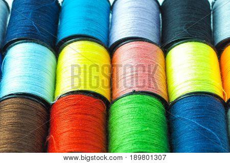 Colorful sewing thread reels background, well arranged