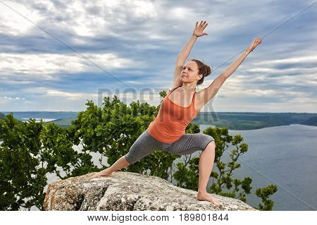 An attractive young woman doing a yoga pose for balance on the rock. Sportive woman in the t-shirt, leggings and barefoot. Practicing yoga against beautiful sky with clouds, tree and big river. Concept of the healthy and active lifestyle.