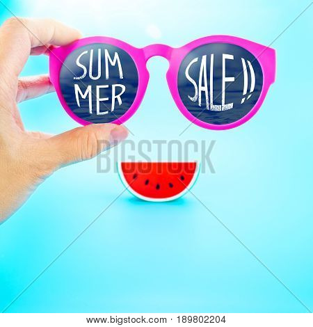 Hand Holding Summer Pink Glasses With Summer Sale! Word And Watermelon At Light Blue Background,summ