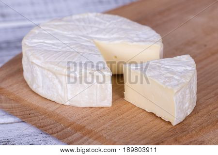 Brie type of cheese. Camembert cheese. Fresh Brie cheese and a slice on a wooden board. Italian French cheese. Close up