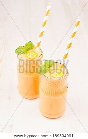 Orange citrus kumquat fruit smoothie in glass jars with straw mint leaf cute ripe berry vertical close up. White wooden board background.