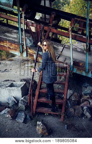 Portrait of a beautiful young blond womanin grey coat, sunglasses, leather pants in an industrial background. Abandoned metal factory.