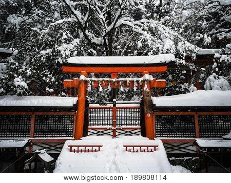 A crimson, shinto gate covered in snow
