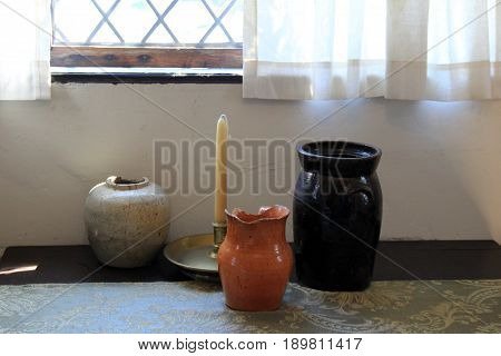 Horizontal image of three clay pots and tapered candle on table of country home.