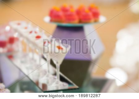 Stylish sweet candy buffe set at the wedding ceremony confectionery out of focus blur background.