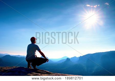 Runner In Red Cap And  In Dark Sportswear. Man Sit  In Squatting Position On A Rock In Heather Bushe