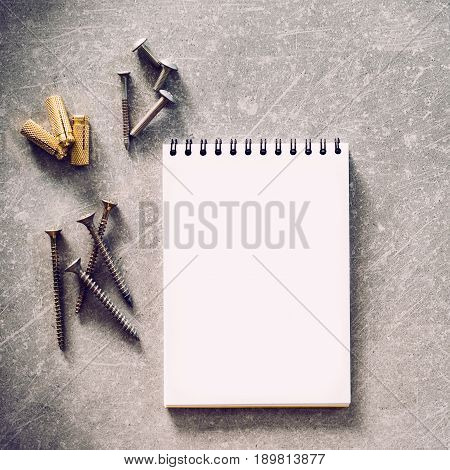 Construction tools. The screws, nuts and bolts arranged around blank spiral bound note book paper on concrete background. Repair, home improvement concept. Free space for text, top view, flat lay