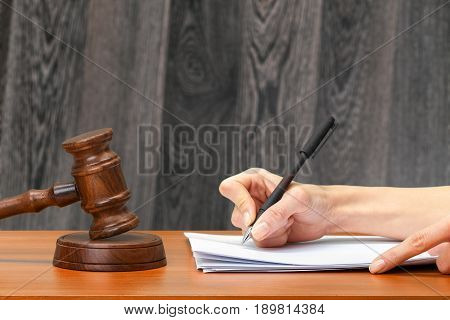 Judge Writing On Paper In Courtroom .