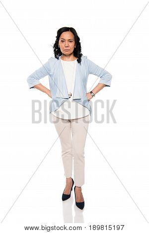 Serious Asian Woman Standing With Hands On Waist Isolated On White