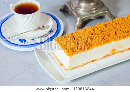 Professional bakery. Exquisite white cheesecake, sprinkled with sweet orange crumbs. The background is porcelain white cup with hot tea and samovar on blue kitchen towel