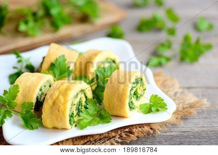 Cheese and parsley omelette rolls on a white plate. Home fried omelette rolls with grated cheese and finely chopped parsley. Tasty low carb egg omelette recipe. Rustic style