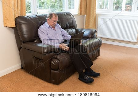 Old Aged Pensioner, Man Sat On Sofa Using A Laptop