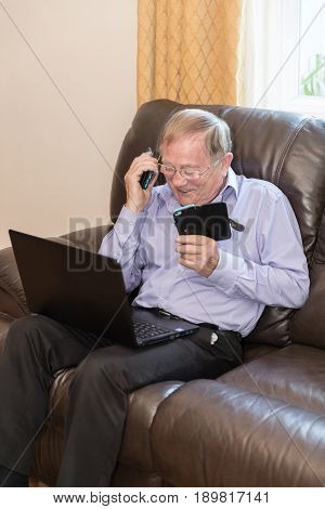 Elderly Man Using A Mobile Phone And Laptop
