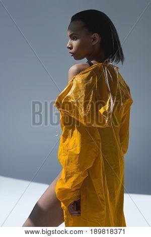 Beautiful Young African American Woman In Wet Yellow Raincoat Posing In Studio