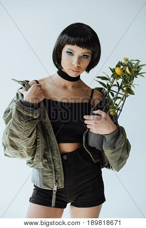 Stylish Woman In Bomber Jacket Holding Lemon Tree In Hands Isolated On Grey