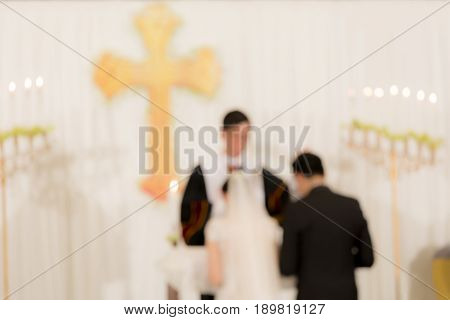 Abstract blurred photo of bride and groom during catholic wedding ceremony in church.