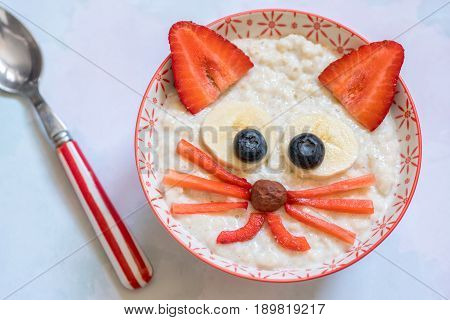 Oatmeal porridge with a cat kitten face decoration. Funny breakfast for kids