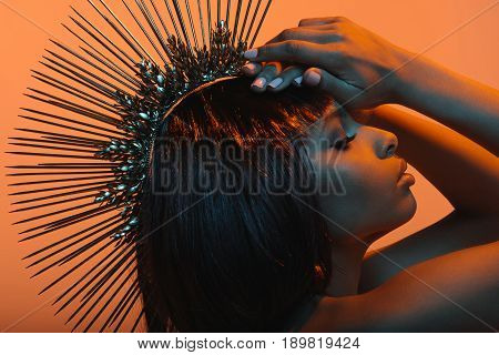 Side View Fashionable African American Woman In Headpiece With Hands On Head