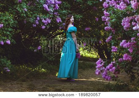 Lovely woman is walking through the garden of a blossoming lilac.