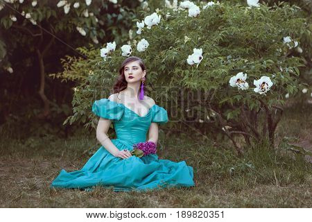 Woman dreams of sitting under a bush in her hands she holds a branch of lilac.