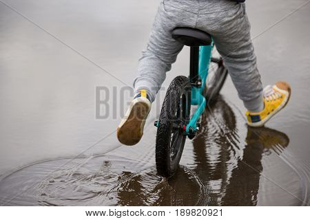 Back view on cute toddler boy riding his bike on water. Child on bicycle on puddle in the park.