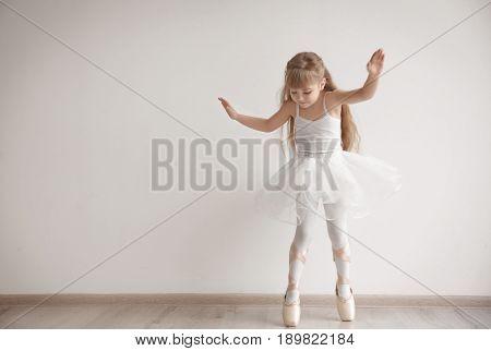 Beautiful little ballerina in light dance studio