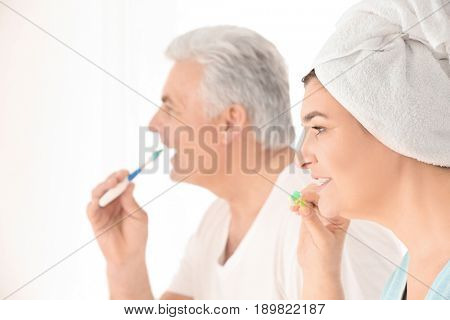 Senior woman and her husband cleaning teeth on light background
