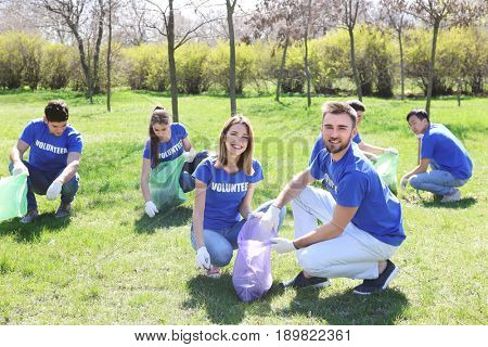 Group of young volunteers gathering garbage in park