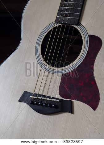 Close up shot of acoustic guitar. Strings sound hole bridge pickguard