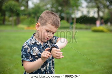 little boy considering watch on his hand