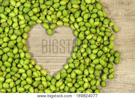 A lot green young walnuts in husks on kitchen table in the shape of heart