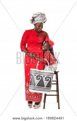 Beautiful African woman and little girl in traditional clothing with wicker tote bag. Isolated on the white studio background