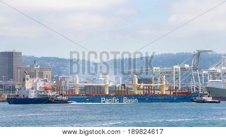 Oakland CA - June 01 2017: A tugboat maneuvers vessels by pushing or towing them. Tugboats VETERAN and PATRIOT assists MOUNT HIKURANGI to maneuver out of the Port of Oakland.
