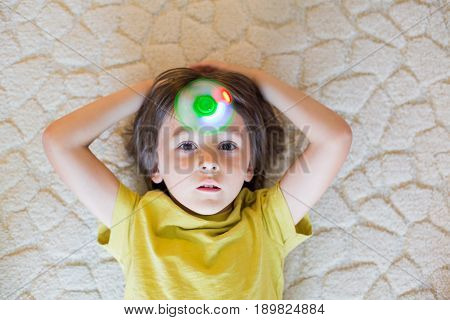 Little Child, Boy, Playing With Green Luminous Fidget