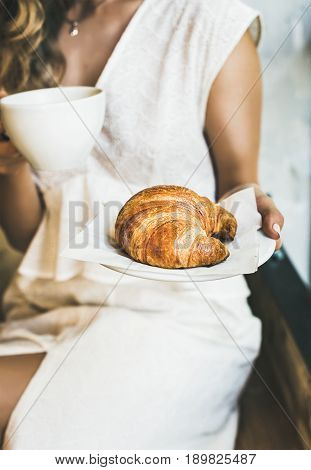 French or Italian breakfast. Young blond woman in white dress holding fresh croissant and cup of cappuccino in cafe